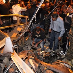 Emergency personnel in Beirut inspect the debris at the site of a twin suicide bombing