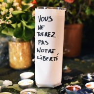 Flowers and a candle reading 'You Will Not Kill Our Freedom' are left on the pavement near the scene of the Nov. 13th Bataclan Theatre terrorist attack