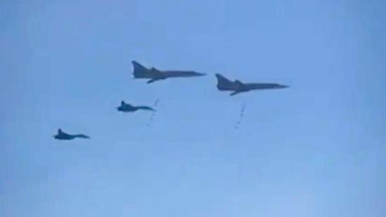 In this photo made from the footage taken from Russian Defense Ministry official web site on Tuesday, Nov. 17, 2015, Russian Tu-22 bombers escorted by the Su-27s fighter jets drop bombs on a target in Syria.